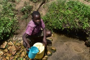 The Water Project: Ematetie Community, Amasetse Spring -  Paul Fetching Water
