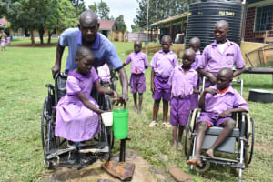 The Water Project: Rise and Shine Special School for the Physically Handicapped -  A Teacher Helps The Students Fetch Water
