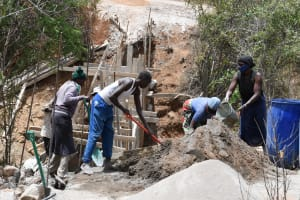 The Water Project: Syonzale Community -  Scooping Cement Onto Top Of Dam Wall