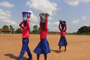 The Water Project: Masoila Roman Catholic Primary School -  Students Carrying Water