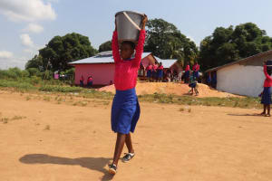 The Water Project: Masoila Roman Catholic Primary School -  Student Carrying Water