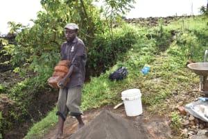 The Water Project: Ikoli Community, Odongo Spring -  Carrying Bricks