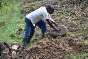 The Water Project: Ikoli Community, Odongo Spring -  Rolling Large Rocks For Backfilling