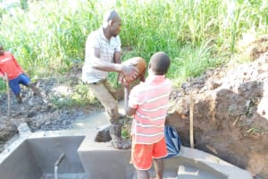 The Water Project: Musango Community, Wambani Spring -  Giving A Helping Hand During Backfilling