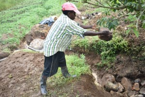 The Water Project: Ikoli Community, Odongo Spring -  Backfilling With Layer Of Large Rocks