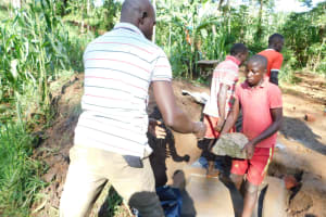 The Water Project: Musango Community, Wambani Spring -  Backfilling With Large Rocks