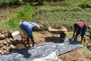 The Water Project: Ikoli Community, Odongo Spring -  Getting Accurate Measurements Of The Polythene Sheet