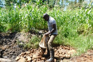 The Water Project: Musango Community, Wambani Spring -  Backfilling With Layer Of Small Stones
