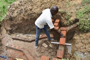 The Water Project: Ikoli Community, Odongo Spring -  Setting The Pipe