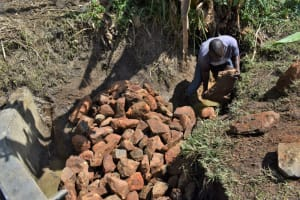 The Water Project: Malekha Central Community, Misiko Spring -  Backfilling With Clay And Rocks