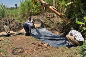 The Water Project: Malekha Central Community, Misiko Spring -  Backfilling With Palstic Tarp