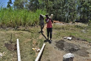 The Water Project: Malekha Central Community, Misiko Spring -  Community Members Relocate The Fence Poles Ready For Use