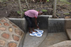 The Water Project: Malekha Central Community, Misiko Spring -  John Making Use Of The Waterpoint