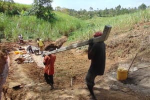 The Water Project: Makhwabuye Community, Majimazuri Lusala Spring -  Community Members Carry Fencing Poles To The Spring