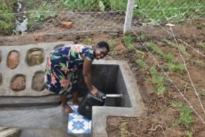The Water Project: Indulusia Community, Wanyama Spring -  A Woman Fetching Water