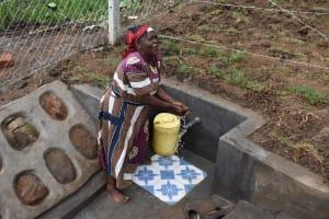 The Water Project: Indulusia Community, Wanyama Spring -  An Elder Enjoying Water