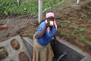 The Water Project: Indulusia Community, Wanyama Spring -  Chair Gladys Enjoys A Drink Of Water