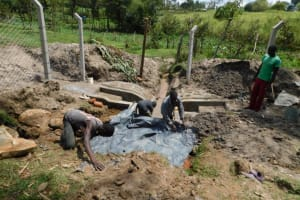 The Water Project: Muyundi Community, Magana Spring -  Backfilling With Plastic Tarp