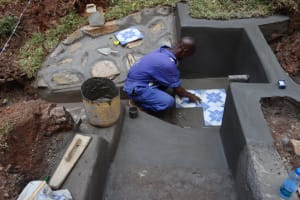 The Water Project: Shamakhokho Community, Wizula Spring -  Artisan Setting Tiles