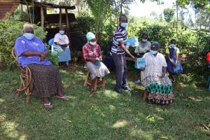 The Water Project: Shamakhokho Community, Wizula Spring -  Facilitator Distributing Training Materials