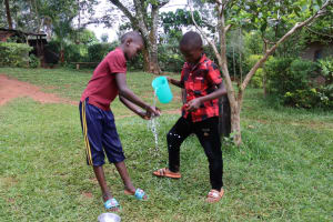 The Water Project: Shamakhokho Community, Wizula Spring -  Rinsing Hands Using Clean Running Water