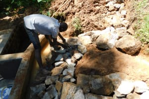 The Water Project: Malekha West Community, Soita Spring -  Backfiling With Large Stones