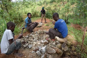 The Water Project: Malekha West Community, Soita Spring -  Breaking Large Stones Into Gravel