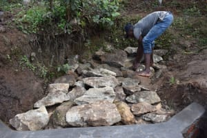 The Water Project: Malanga Community, Malava Housing Spring -  Backfilling With Large Stones