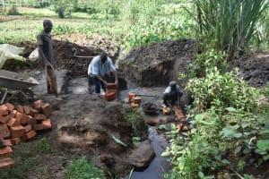 The Water Project: Malanga Community, Malava Housing Spring -  Community Members Help Pass Bricks To The Artisan