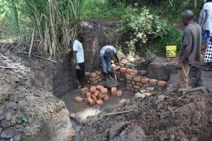 The Water Project: Malanga Community, Malava Housing Spring -  Pipe Setting