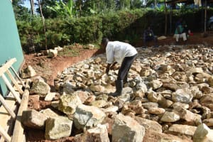 The Water Project: Friends School Manguliro Secondary -  Compacting Stones In The Excavated Area