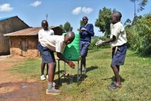 The Water Project: Kapsegeli KAG Primary School -  Boys Using Handwashing Station