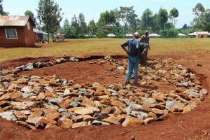 The Water Project: Kapkeruge Primary School -  Laying Stones At Excavated Site
