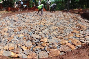 The Water Project: Kapkeruge Primary School -  Arranging Wire To Compact Stones