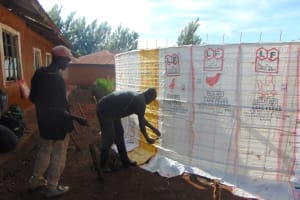 The Water Project: Kapkeruge Primary School -  Tying Sacks To Wire
