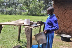 The Water Project: Bukhakunga Primary School -  A Pupil Puting Utensils On The Dish Rack