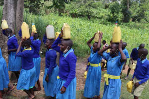 The Water Project: Bukhakunga Primary School -  Pupils Carrying Water To School