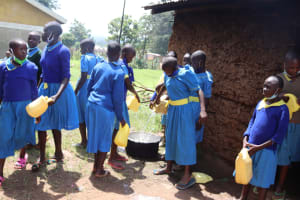 The Water Project: Bukhakunga Primary School -  Pupils Pouring Water Into Storage Pots At School