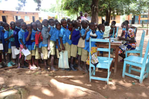 The Water Project: Bukhakunga Primary School -  Pupils Queueing To Submit Their Assignments To A Teacher