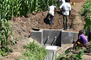 The Water Project: Ematetie Community, Amasetse Spring -  Back Filling With Soil