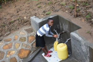 The Water Project: Ematetie Community, Amasetse Spring -  Happy Child Fetching Water