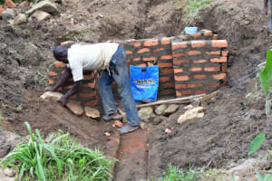 The Water Project: Ematetie Community, Amasetse Spring -  Placing Large Stones