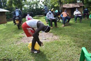 The Water Project: Musango Community, Wambani Spring -  A Boy Shows How To Make A Leaky Tin Handwashing Station