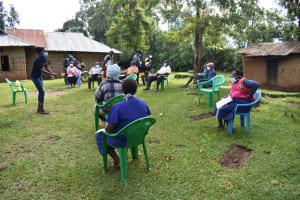 The Water Project: Musango Community, Wambani Spring -  Trainer Taking Them Through Ten Handwashing Steps
