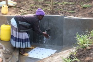 The Water Project: Ikoli Community, Odongo Spring -  Community Member Washing Hands Before Fetching Water