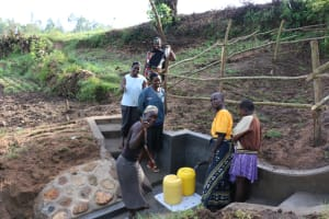 The Water Project: Ikoli Community, Odongo Spring -  Women Collecting Water
