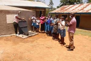 The Water Project: St. Benedict Emutetemo Primary School -  Trainer Jacky Handing Over Rain Tank