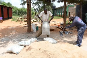 The Water Project: Mukuku Mixed Secondary School -  Dumping Cement Bags To Mix With Sand