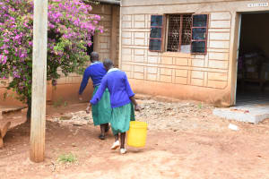 The Water Project: Migwani DEB Primary School Rain Tank -  Girls Carrying Water