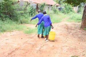 The Water Project: Migwani DEB Primary School Rain Tank -  Students Carrying